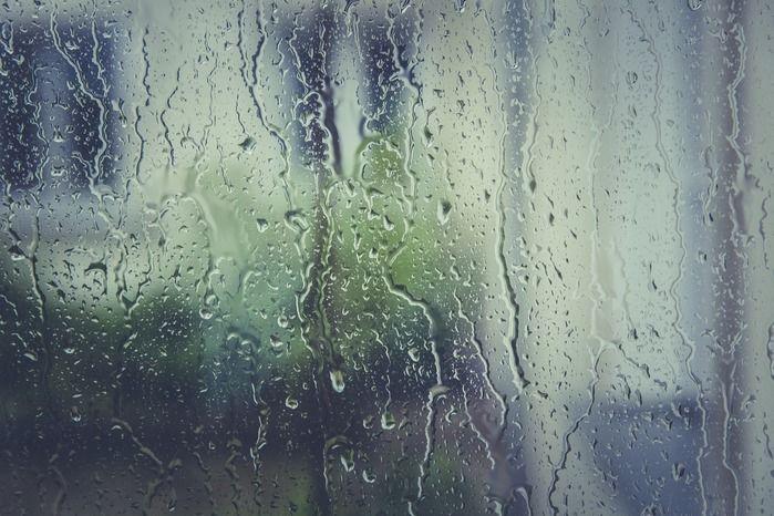 窓にかかった雨の水滴が流れ落ちる様子
