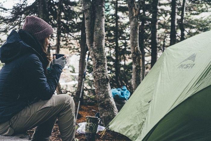 テントの横で寒そうにマグカップを持つマウンテンパーカーを着た女性