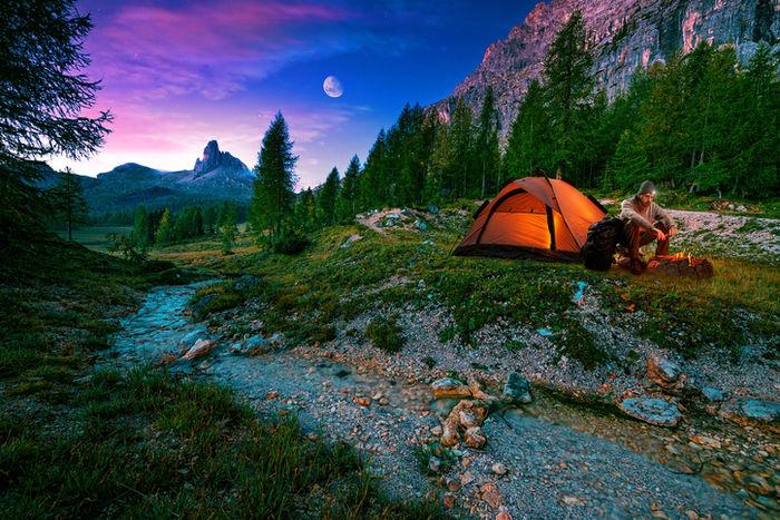 川辺でソロキャンプをする男性