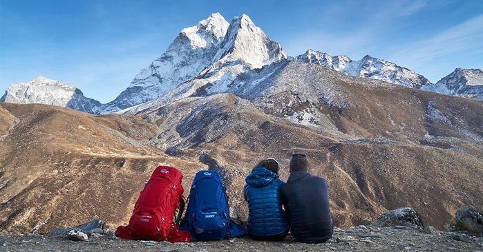 険しい山々を前に座っている男女の後ろ姿