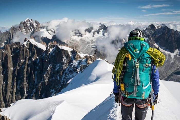 ロウアルパインのリュックを背負って雪山を歩く人