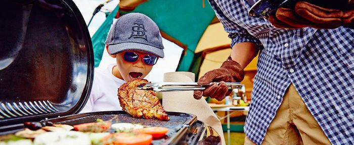 バーベキューのお肉を食べる子供