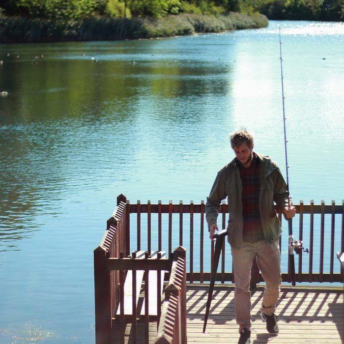 釣り竿とSITPACKを持つ男性