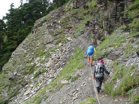 岩肌むき出しの山道をロープを伝って登る人々
