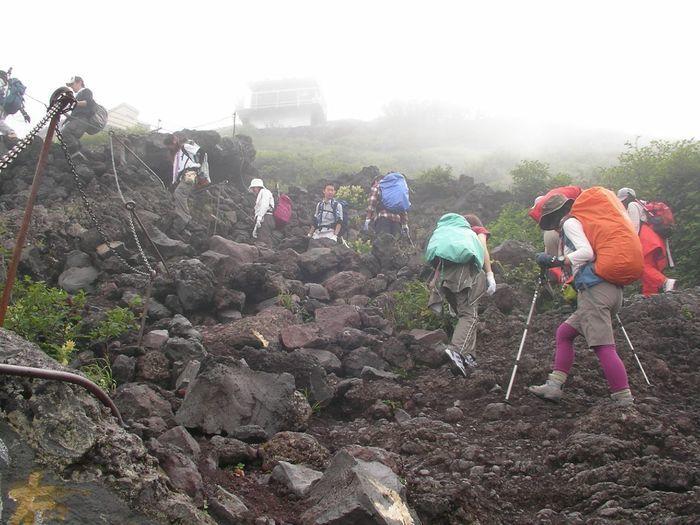 山の岩肌を列になって登る人々