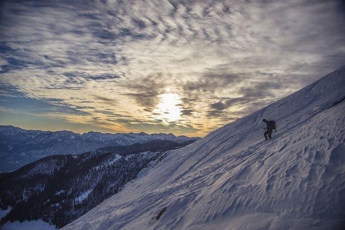 雪山で登山をする男性