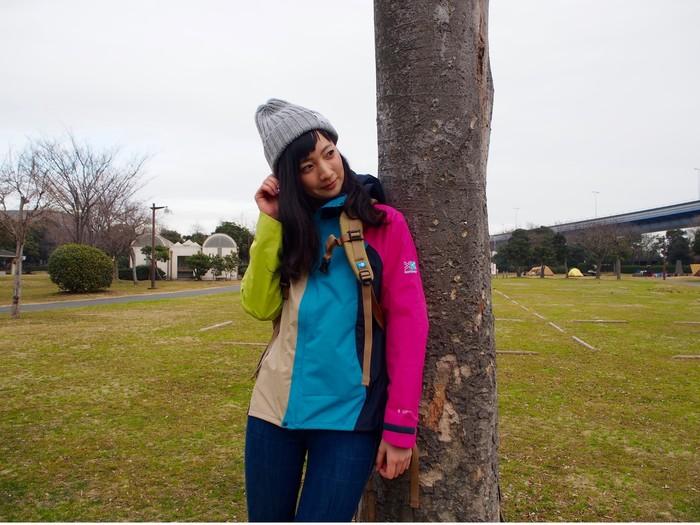 木にもたれかかるカリマーのジャケットを着た女性