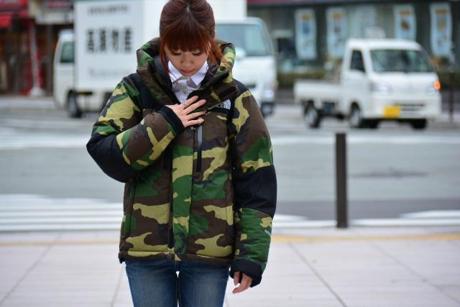 ノースフェイスのカモ柄のジャケットを着る女性