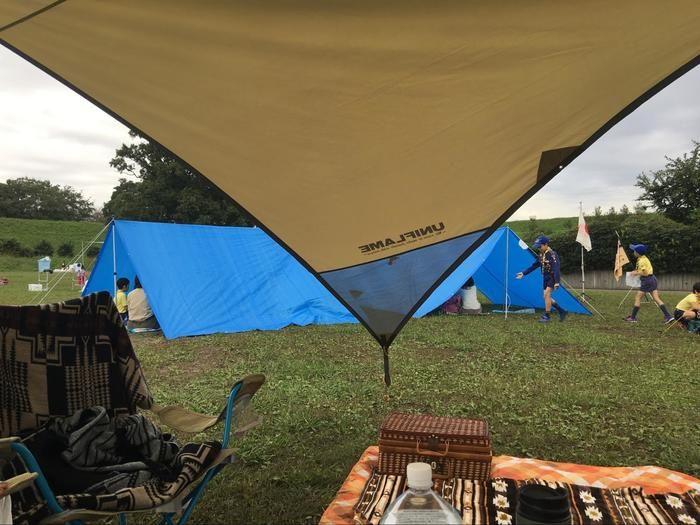 ボーイスカウトの子供達がブルーシートを使って テントを張っている様子