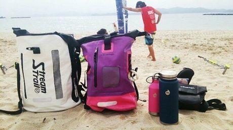 砂浜に置かれたストリームトレイルのバッグと水筒