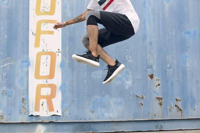 Tevaのスニーカーを履いてジャンプする男性