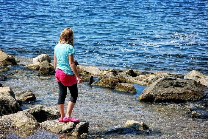 海の岩場に立つ女性