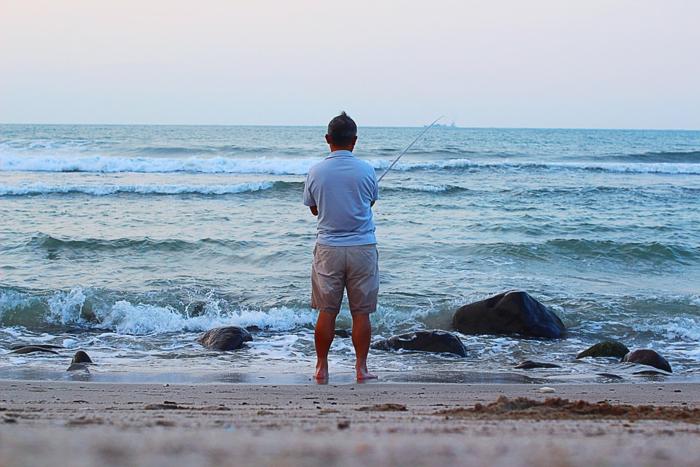浜辺で釣りをする男性