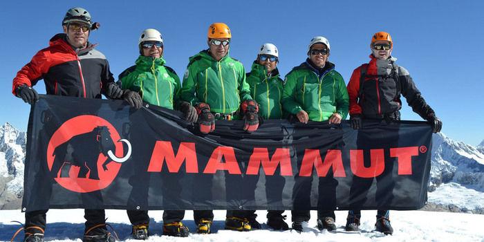 雪山の上でマムートのロゴを掲げる男性