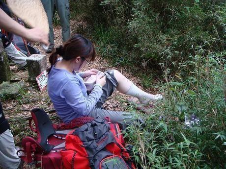 登山道で休憩する女性