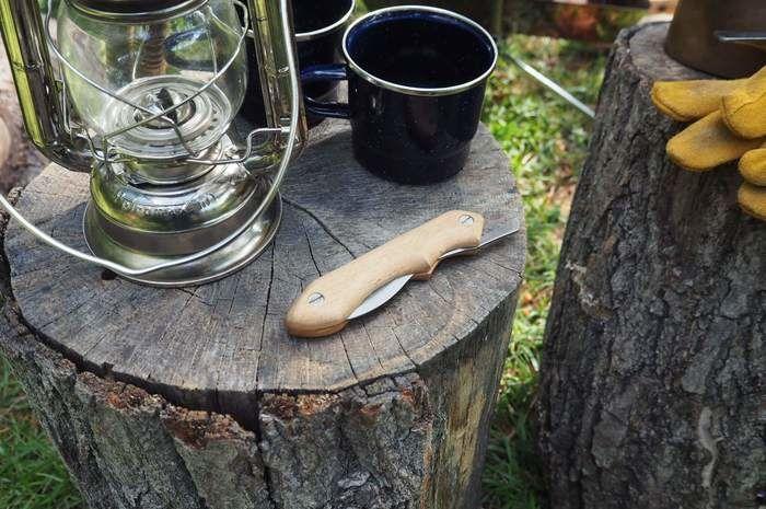 切り株に置かれたランタンと折り畳みナイフ
