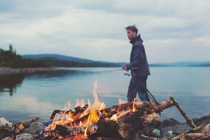 池で釣りをする人と焚き火