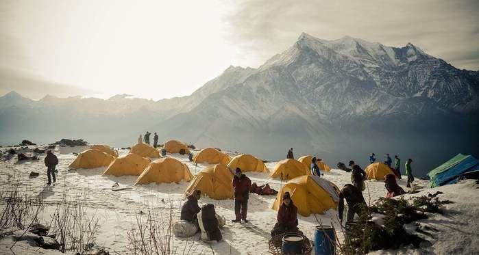 雪山でキャンプをするモンテインのジャケット着た人々