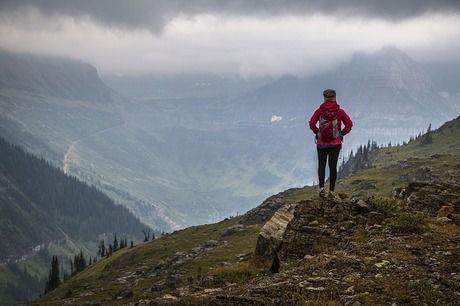 山の山頂付近から雲に隠れた山並みを眺める女性
