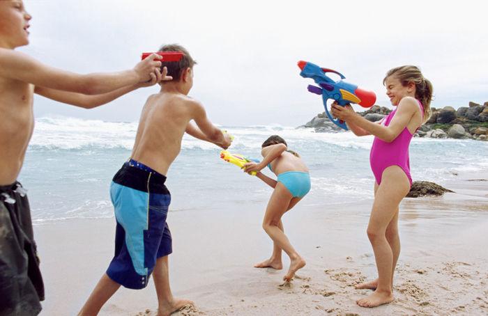 砂浜で水遊びをする子供たち