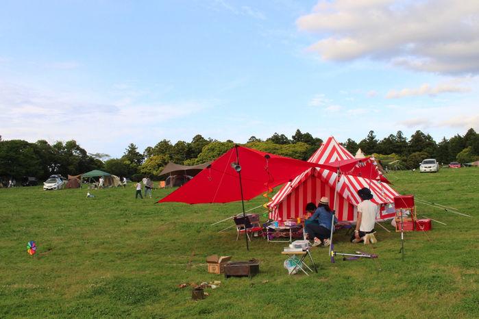 森のまきばオートキャンプ場でテントを張りキャンプを楽しむ人々
