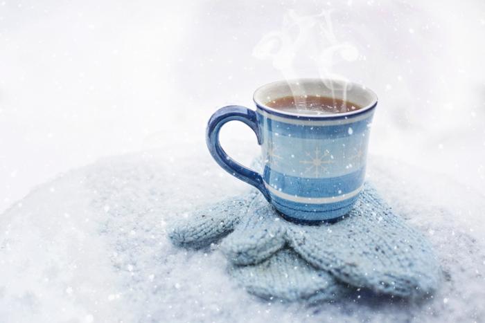 雪の中ミトンの上に置かれたホットコーヒー