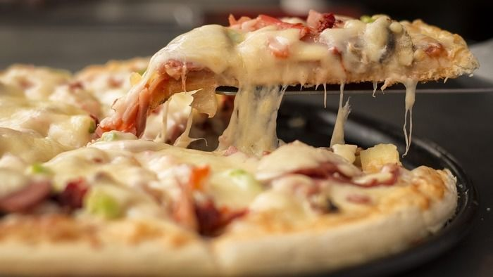 玉ねぎとベーコンのピザをとり分ける様子