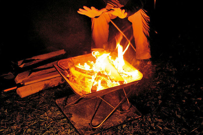 揺らめく焚き火と焚き火に当たる人