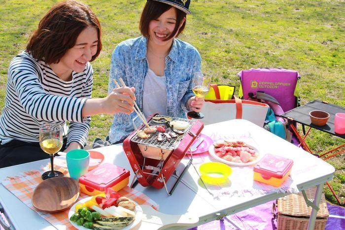 ピクニックでコンパクトグリルを使ってBBQする女性2人