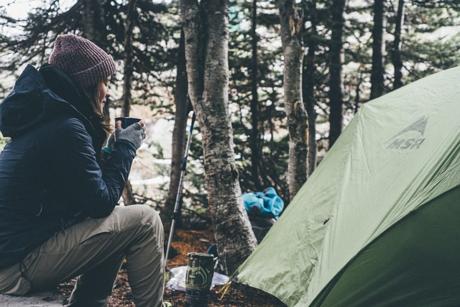 ドーム型テントの横でお茶を飲んで一息つく人