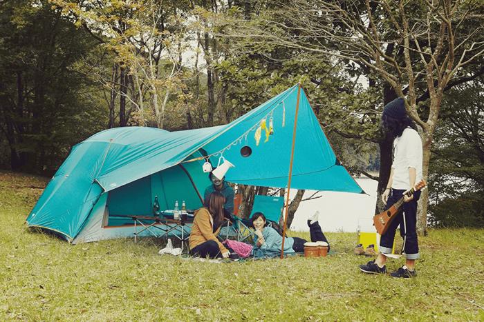 ドーム型テントの前室でキャンプを楽しむ人々
