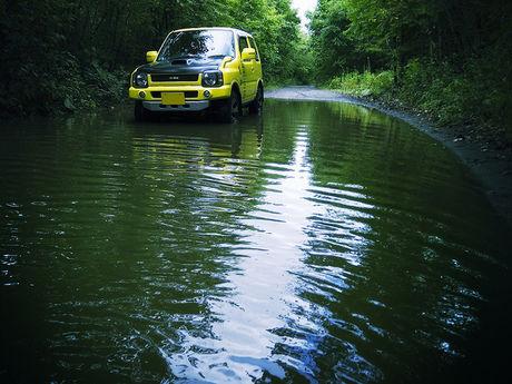 水たまりを走る軽自動車
