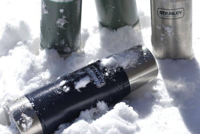 雪の上に置かれたスタンレーの水筒