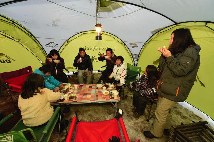 夜ご飯をテントの中で食べる人々
