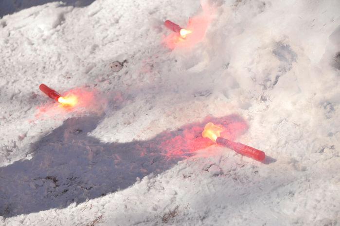 雪の上に置かれた発煙筒