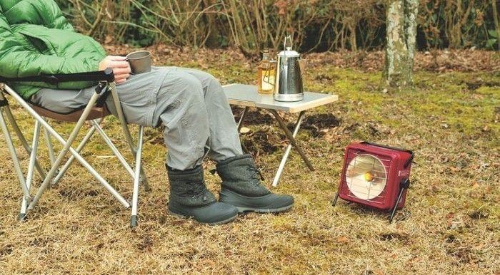 キャンプチェアでくつろぐ男性と電気ヒーター