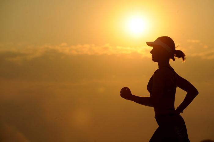 夕日と走る女性の影