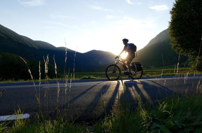 坂道を自転車で降る男性
