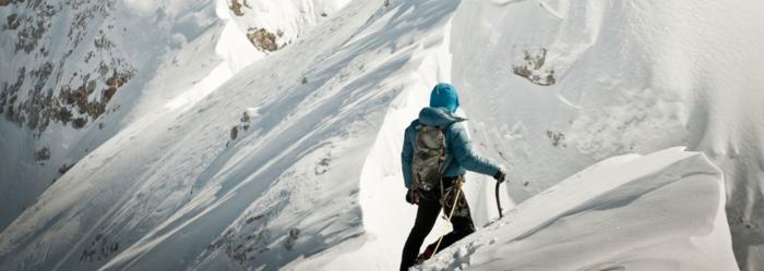 険しい雪山を登る男性の後ろ姿
