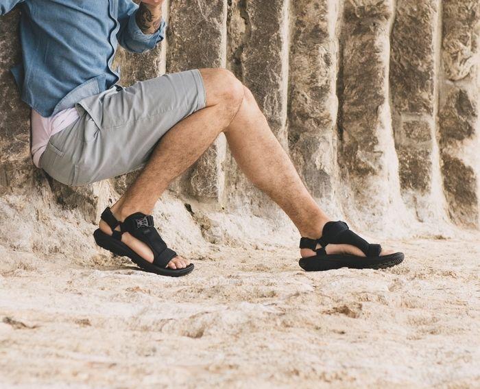 Tevaのサンダルを砂浜で履く男性