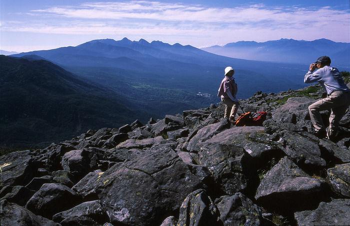 蓼科山の岩場に立って写真撮影をする人