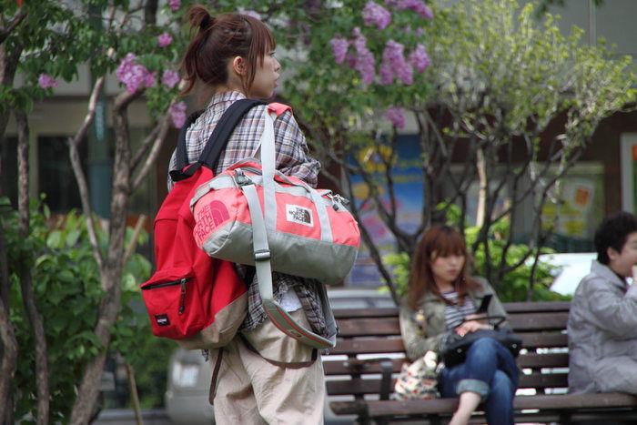 ノースフェイスのバッグを持って街を歩く女性