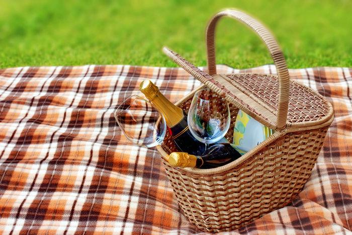 ピクニックバスケットに入れられたワインボトルとグラス