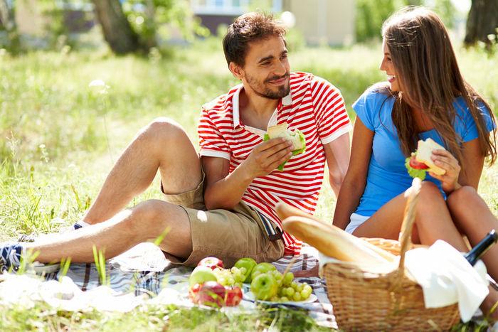 サンドイッチを食べてピクニックを楽しむカップル