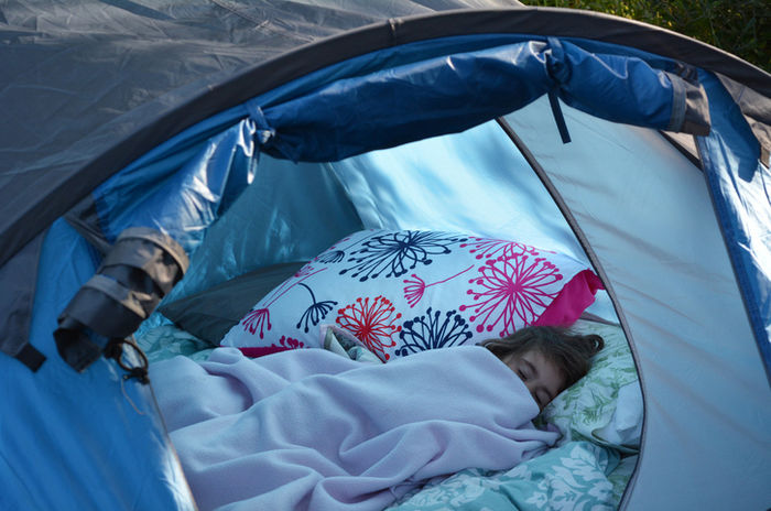 テントの中で毛布にくるまって寝る女の子