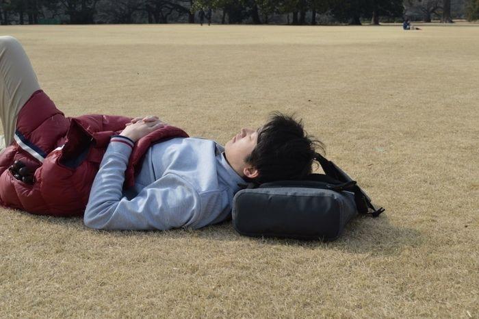 クラウドファンディングの「code10」を枕にして寝ている男性