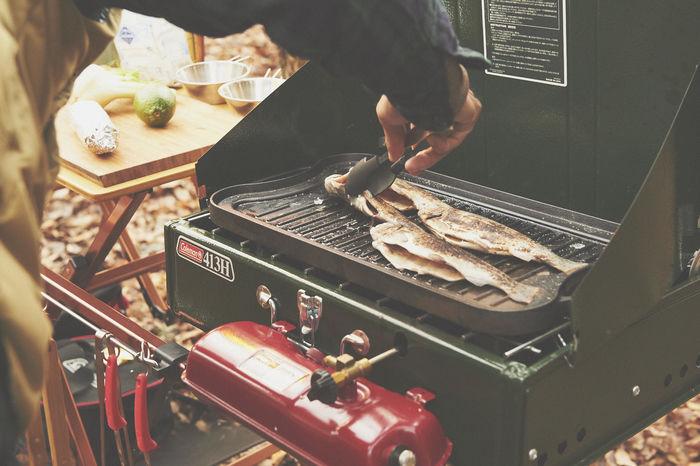 コールマンのツーバナーを使いお肉を焼く男性