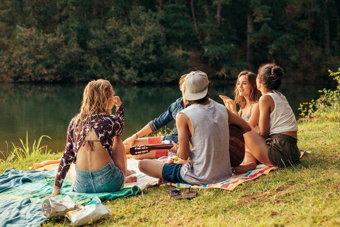 川沿いの芝生でピクニックを楽しむ男女