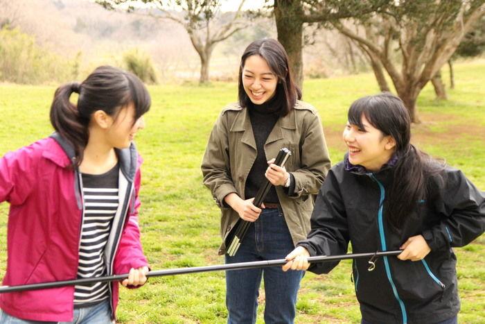 楽しげにメインポールを組み立てている女性3人