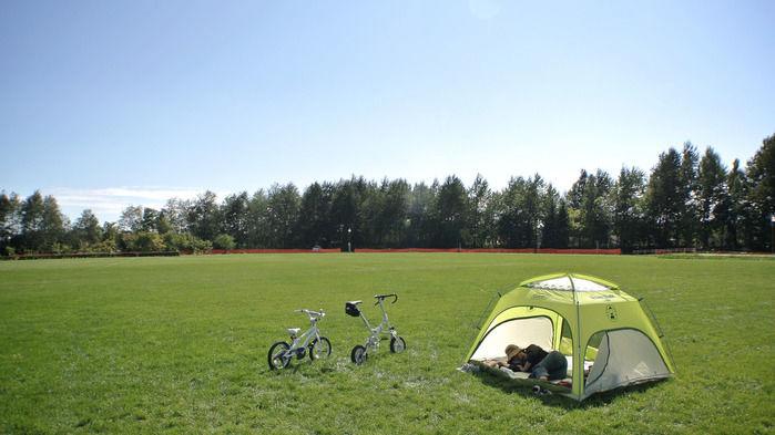 芝生の上のサンシェードで眠る男性と自転車
